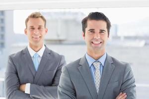 due uomini d'affari che sorridono alla macchina fotografica foto