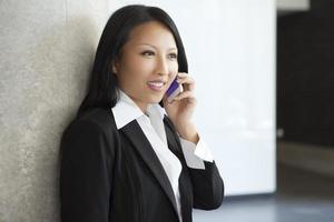 la donna di affari asiatica comunica con il suo cellulare foto