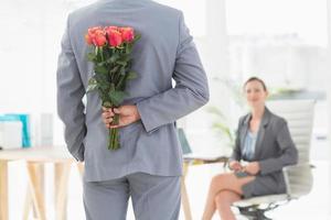 uomo d'affari che tiene i fiori dietro la schiena foto