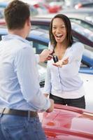donna che raccoglie le chiavi della nuova auto foto