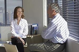 due uomini d'affari che parlano dalla finestra foto