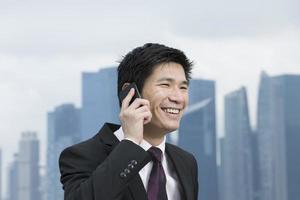 uomo d'affari asiatico al telefono di fronte alla città foto