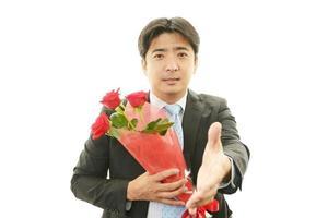 uomo che tiene il mazzo di fiori