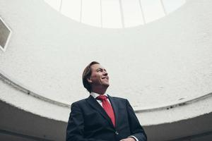 soddisfatto felice giovane imprenditore in piedi sotto la cupola della luce. foto