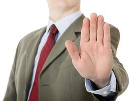 uomo d'affari che ostacola gesto di mano della palma di arresto foto