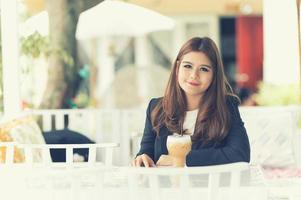 donna di affari dell'Asia che si siede nel caffè con caffè ghiacciato
