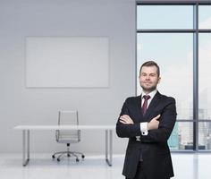 uomo d'affari bello sorridente in un abito nero con le braccia incrociate. foto