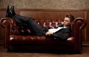uomo in giacca e cravatta sdraiato sul divano foto