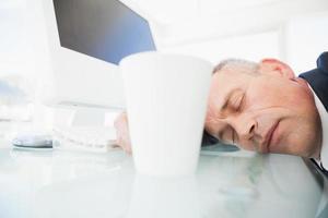 uomo d'affari addormentato nel suo ufficio foto