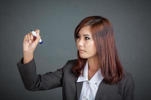 la ragazza asiatica di affari scrive nell'aria foto