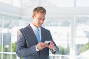 uomo d'affari che manda un sms con il suo smartphone foto