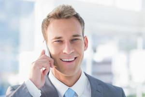 uomo d'affari sorridente che rivolge al telefono foto