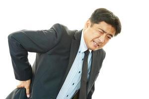 uomo d'affari che ha mal di schiena foto