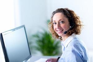 Ritratto di un operatore telefonico giovane e bella donna foto