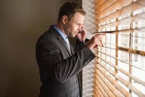 uomo d'affari che dà una occhiata attraverso i ciechi mentre su chiamata foto