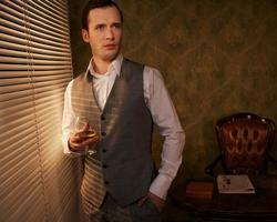 uomo retrò con un bicchiere in piedi vicino alla finestra. foto