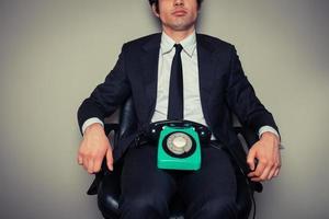 uomo d'affari con il telefono in sedia da ufficio foto