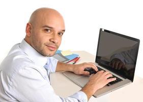 uomo d'affari latino felice calvo che lavora alla macchina fotografica sorridente del computer foto