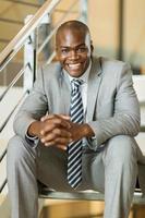 uomo d'affari africano che si siede sulle scale foto