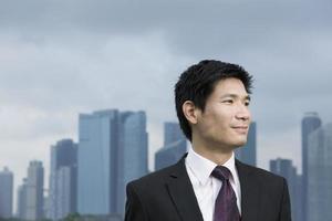 felice uomo d'affari asiatico di fronte alla città.