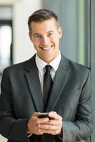 uomo d'affari caucasico che per mezzo dello Smart Phone foto