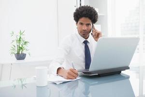 uomo d'affari in camicia telefonando e prendendo appunti foto