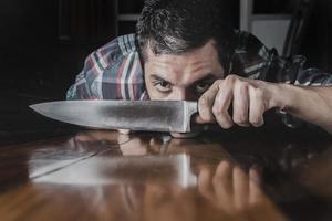 giovane ispanico che tiene un coltello da cucina foto