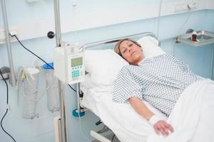 paziente femminile disteso su un letto medico con gli occhi socchiusi