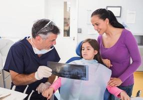 dentista pediatrico che spiega al giovane paziente foto