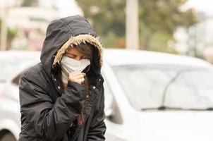 ragazza che cammina indossando giacca e una maschera in foto