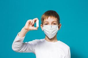 maschera di protezione del ragazzo che tiene le pillole foto