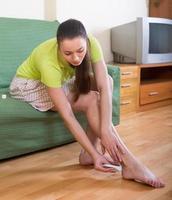 ragazza che tratta i piedi con unguento foto