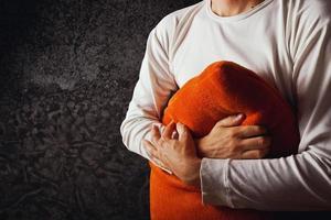 uomo che abbraccia il cuscino arancione foto