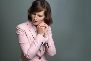 giovane donna seria con le mani giunte in preghiera foto