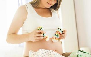 donna incinta con vestiti per bambini foto