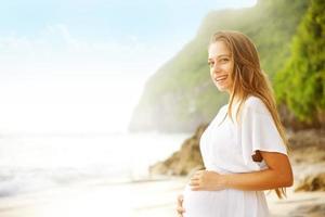 donna incinta in abito bianco sulla spiaggia