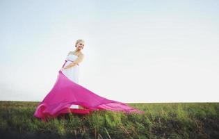 bella giovane donna incinta in abito bianco greco fuori