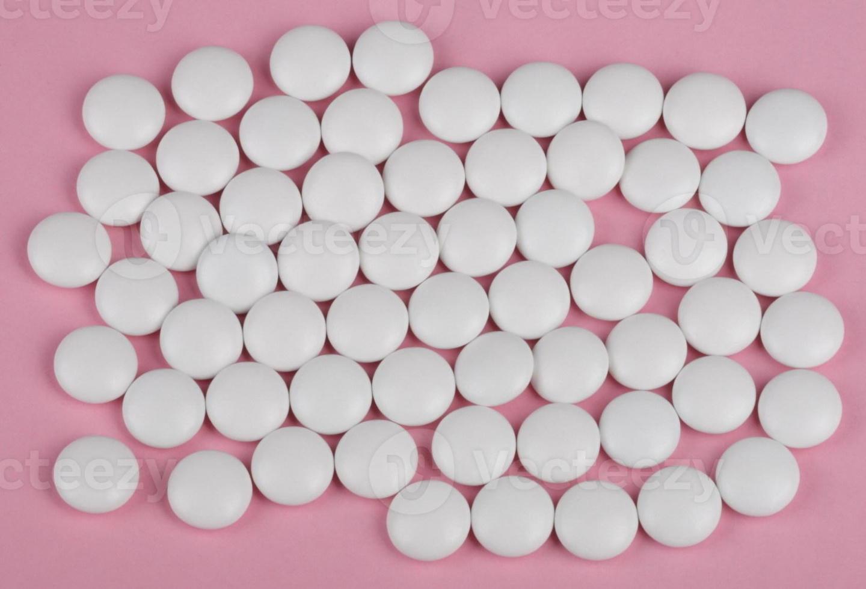 comprimido branco sobre fundo rosa foto
