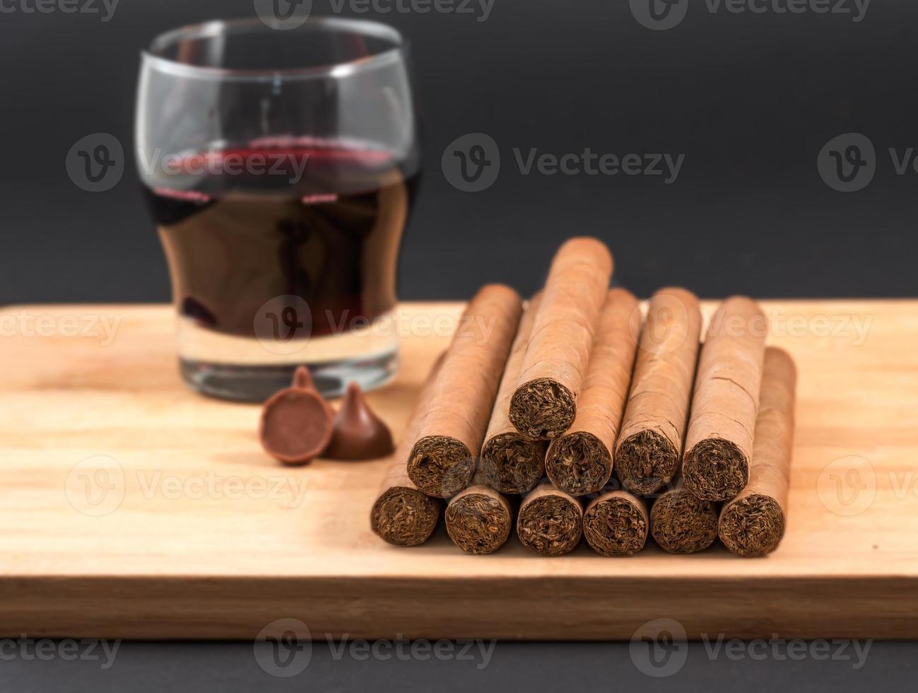 mundialmente famosos charutos cubanos enrolados à mão com vinho tinto foto