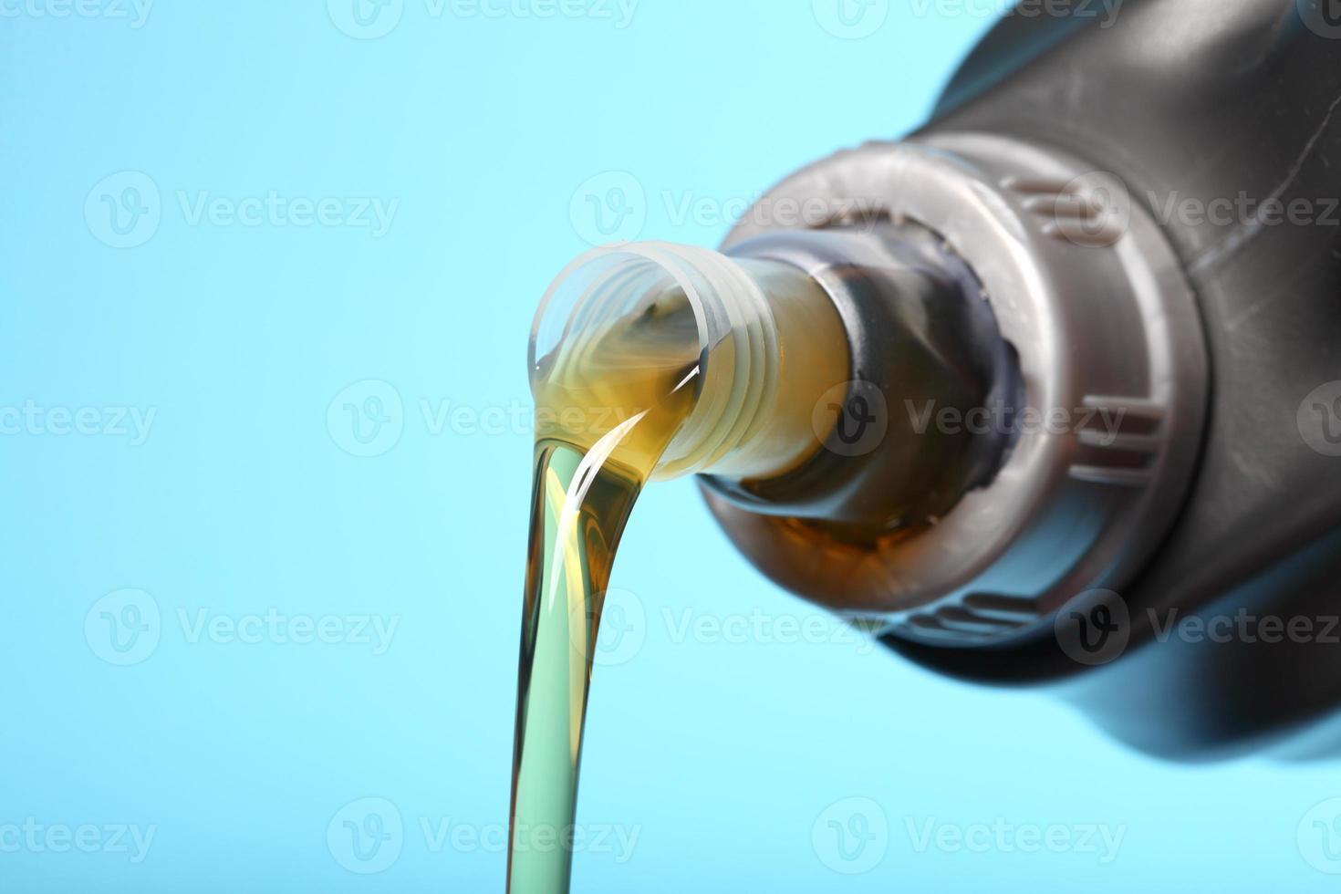 lata com óleo de motor de carro derramando fundo azul foto