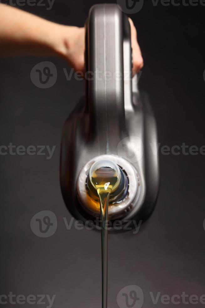 lata com óleo de motor de carro derramando fundo preto foto