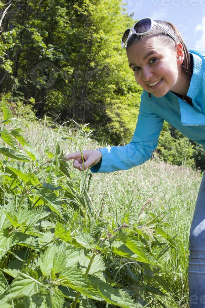 menina tocando folhas de urtiga foto