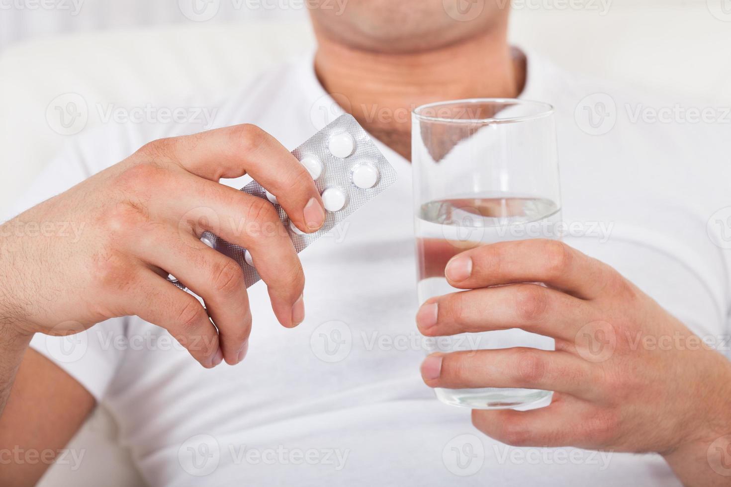 homem com embalagem de comprimidos e copo de água foto