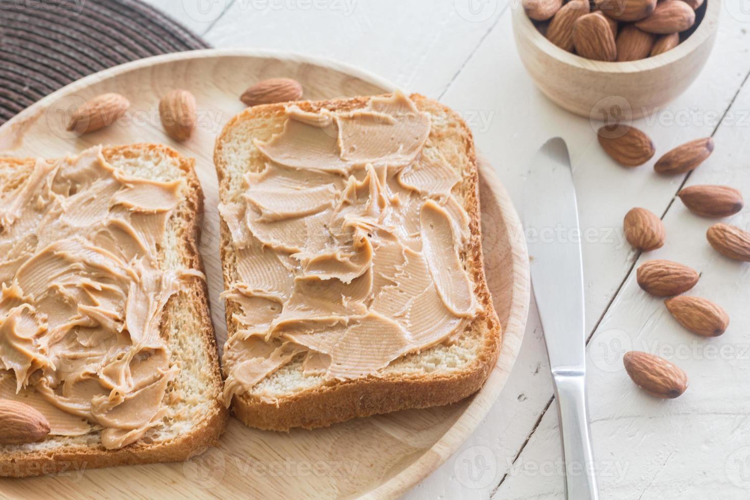 manteiga de amendoim na placa de madeira com nozes na mesa de madeira foto