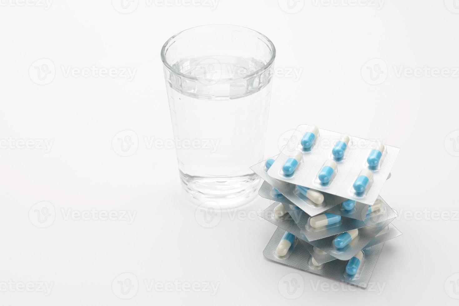 cápsulas embaladas e copo de água foto