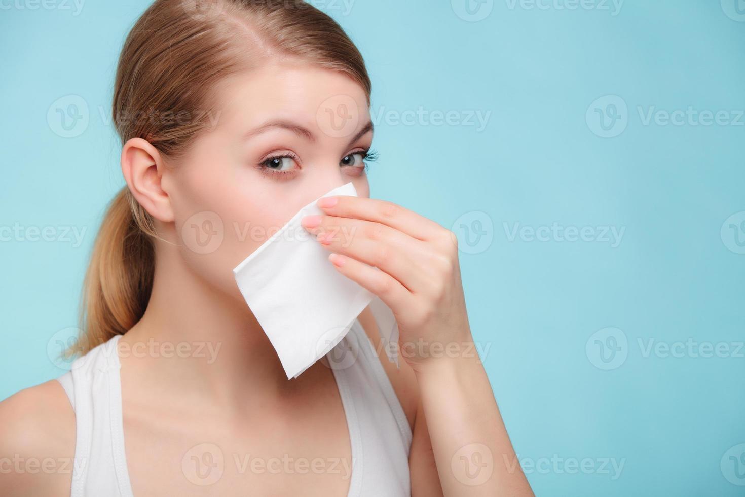 alergia à gripe. garota doente espirros em tecido. saúde foto