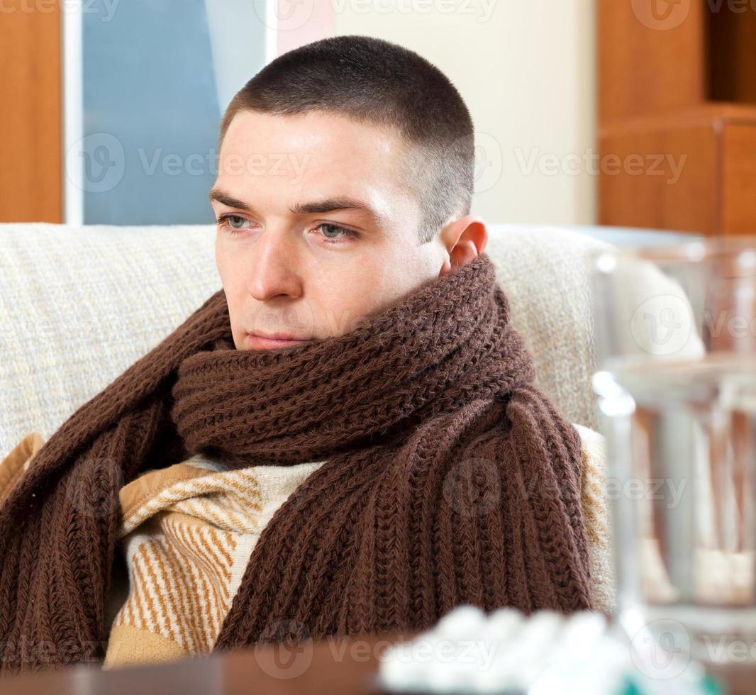 homem triste doente em cachecol quente foto