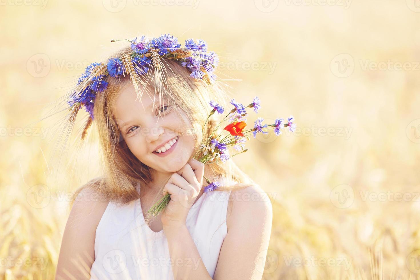 menina feliz com coroa de flores no campo de trigo de verão foto