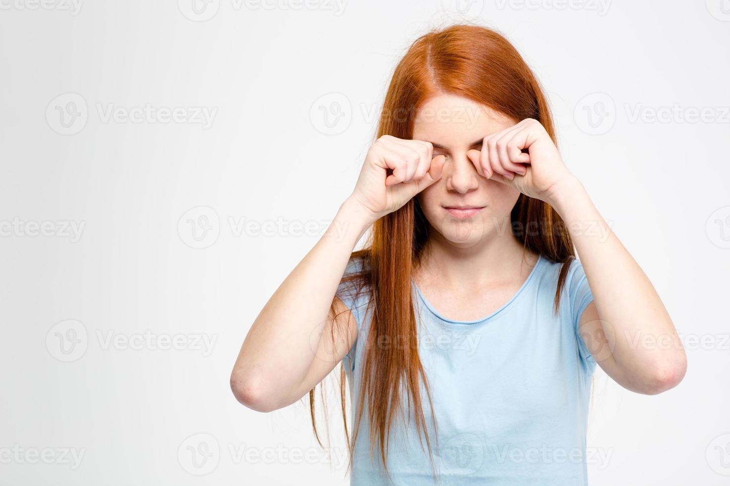 sonolenta jovem cansada, esfregando os olhos pelas mãos foto
