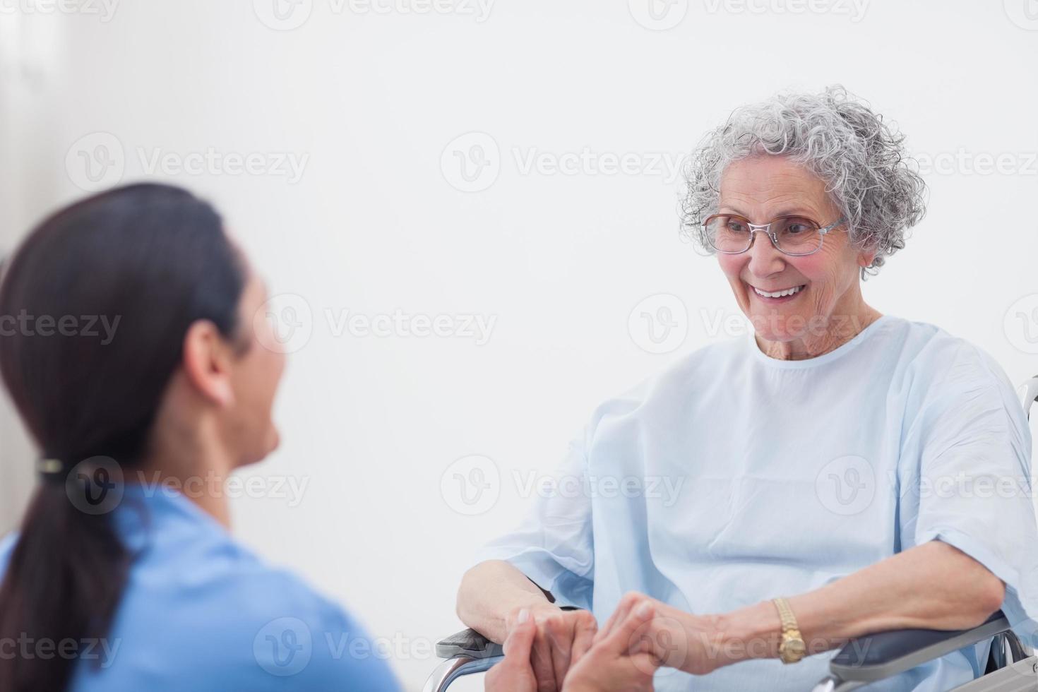 enfermeira, segurando as mãos de um paciente foto